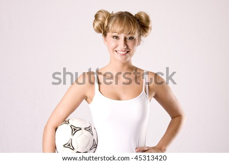 young blond woman in white sportswear is posing with a football - stock photo