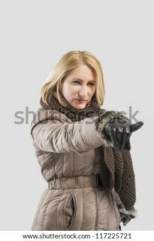 young blond woman in winter clothes pointing forward against gray background