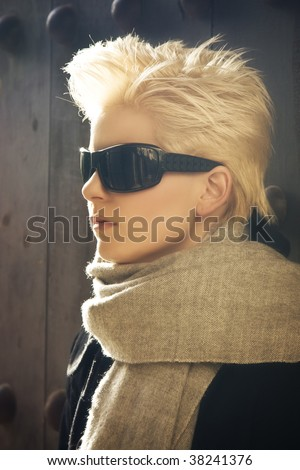 Young blond woman in winter fashion wearing sunglasses. - stock photo