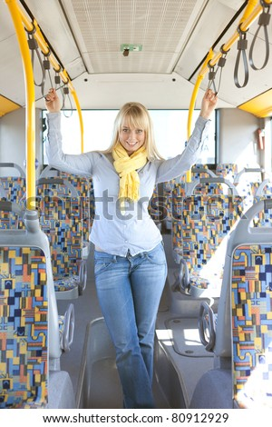 young blond woman inside a bus holds on tight to handles/young blond woman inside a bus holds on tight to handles - stock photo
