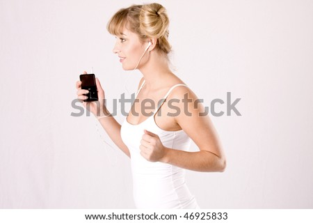young blond woman is jogging and hears music with a mp3 player - stock photo
