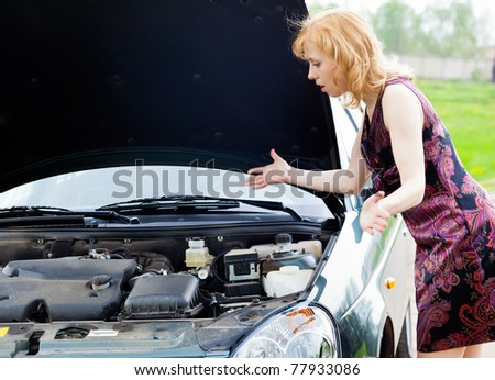 Young blond woman is near a broken car - stock photo
