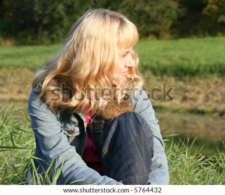 young blond woman is sitting on a grass - stock photo