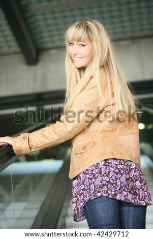 young blond woman is standing on an escalator