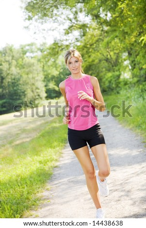 Young blond woman jogging on pathway in park - stock photo