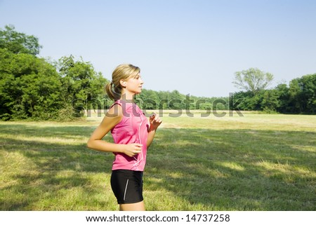 Young blond woman jogging on pathway in park, listening to music - stock photo