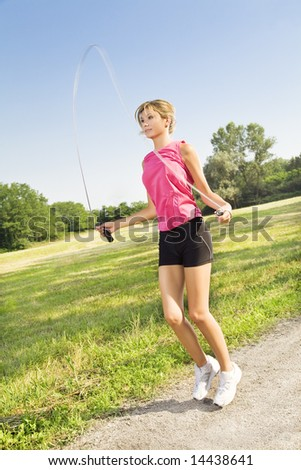 Young blond woman jumping rope at the park. - stock photo