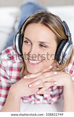 young blond woman listening music with headphones - stock photo