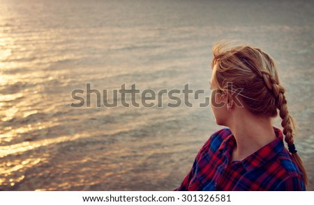young blond woman looking at setting sun - stock photo