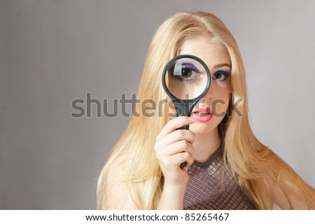 Young blond woman looking through a magnifying glass - stock photo