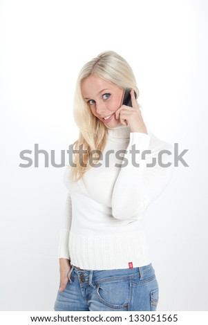 young blond woman makes a call with her smartphone/blond woman phones with a smartphone/woman with her smartphone