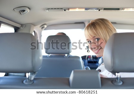 young blond woman on a backseat of a car/young blond woman on a backseat of a car smiles