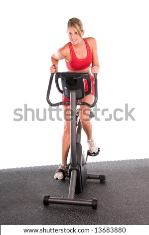 Young blond woman on an exercise bike in the gym - stock photo