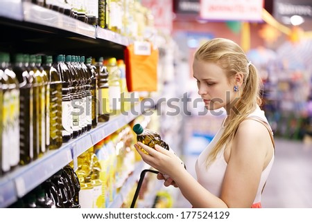 Young blond woman picking an olive oil bottle from the shelves of a supermarket and reading the label - stock photo