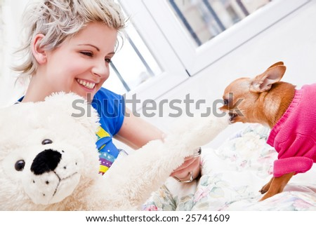 Young blond woman playing with her pet. - stock photo