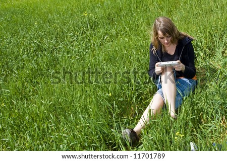 Young blond woman playing with portable machine - stock photo