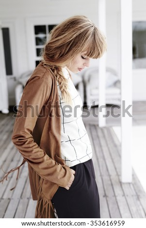 Young blond woman posing on porch, looking down - stock photo