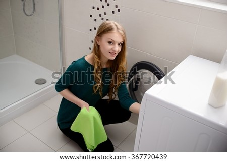 Young blond woman puts dirty laundry into the washing machine - stock photo
