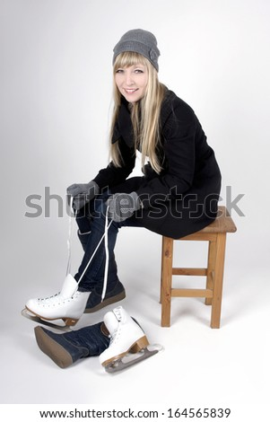 Young blond woman putting on ice scates - stock photo