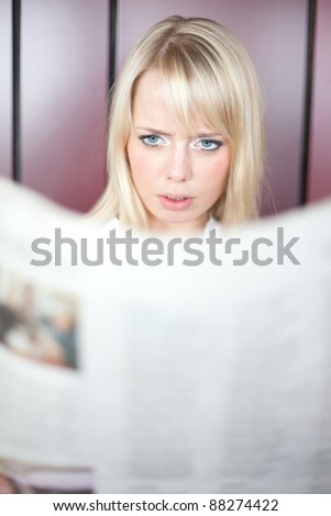 young blond woman reads in a newspaper and is frightened/woman with a newspaper - stock photo