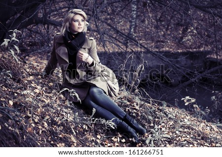 Young blond woman relaxing in autumn forest - stock photo