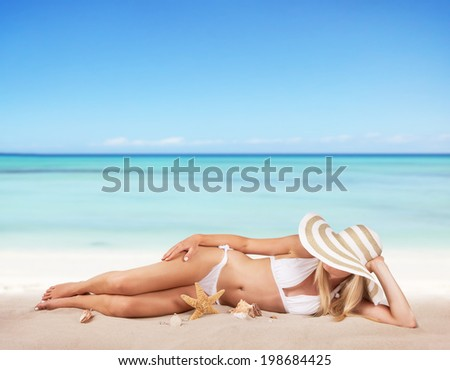 Young blond woman relaxing on beach, blur sea as background