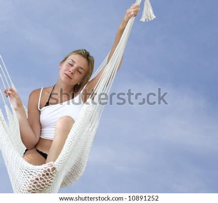 Young blond woman resting in a hammock on a blue sky background - stock photo