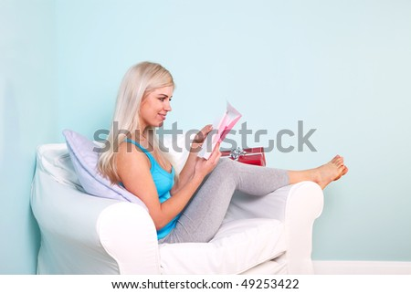Young blond woman sat in an armchair opening her birthday card.
