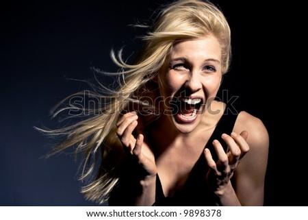 young blond woman screaming,  studio shot - stock photo