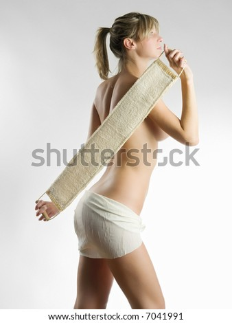 young blond woman scrubbing her shoulder after a shower - stock photo