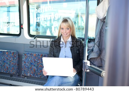 young blond woman sits with a laptop inside a bus/young blond woman as a passanger with a laptop inside a bus