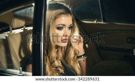 Young blond woman sitting on a backseat of a luxury car at night  - stock photo