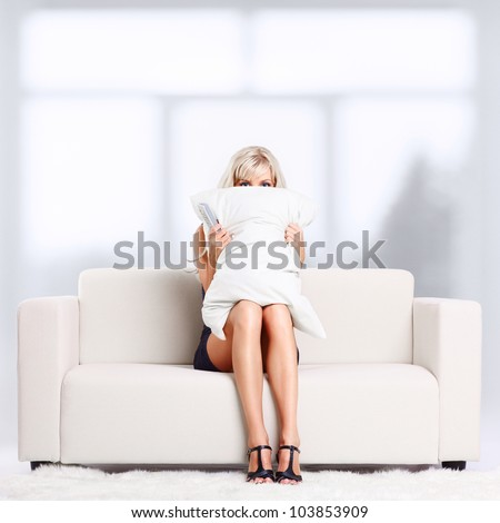 Young blond woman sitting on couch with remote control watching Halloween scary movie and hiding behind the pillow - stock photo