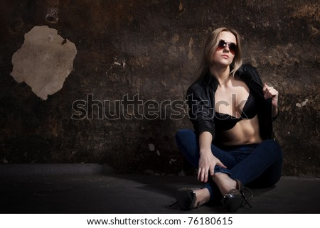 Young blond woman sitting on the floor of an dark old wall - stock photo