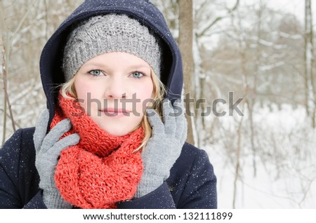 young blond woman smiles with grey beanie and orange scarf in the winter wood