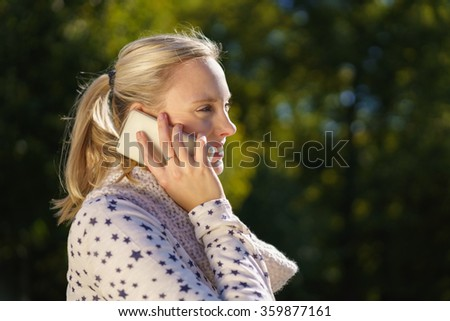Young blond woman standing outdoors in profile against greenery chatting on her cellphone or mobile phone, close up view