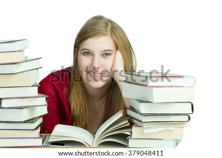 Young blond woman studying with stacks of books