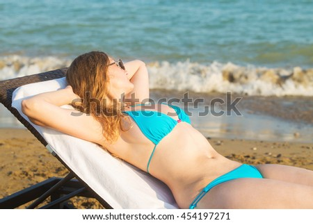 Young blond woman takes sunbathing on lounger on the beach near the sea.