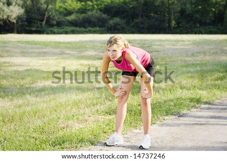 Young blond woman taking breath after jogging - stock photo