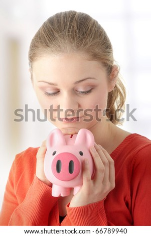 Young blond woman trying to get money from her piggy bank
