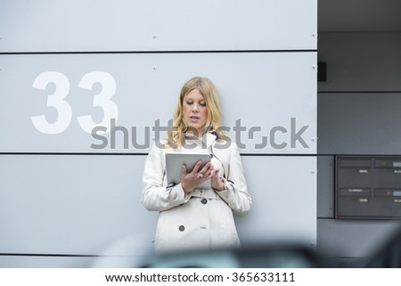 Young blond woman using a tablet computer outdoors a she leans against a commercial building alongside the number 33