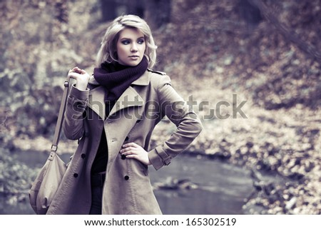 Young blond woman walking in autumn forest - stock photo