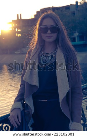 Young blond woman walking in sunglasses, retro portrait of a beautiful girl backlit , instagram style - stock photo