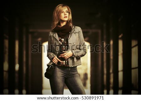 Young blond woman walking in the mall gallery Female stylish fashion model with handbag outdoor