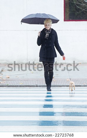 Young blond woman walking with her pet under rain. - stock photo