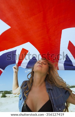 Young blond woman waves British national flag - stock photo