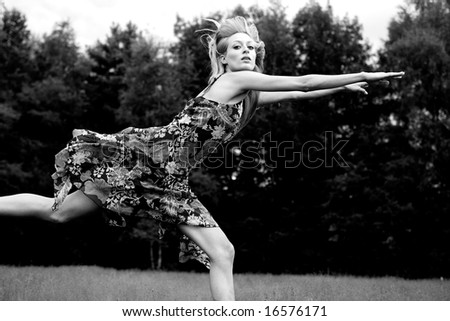 Young blond woman wearing a dress in the forest