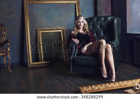 young blond woman wearing crown in fairy luxury interior with empty antique frames total wealth long legs - stock photo