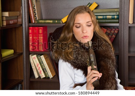 Young blond woman wearing fur sitting with a pistol in her hands - stock photo