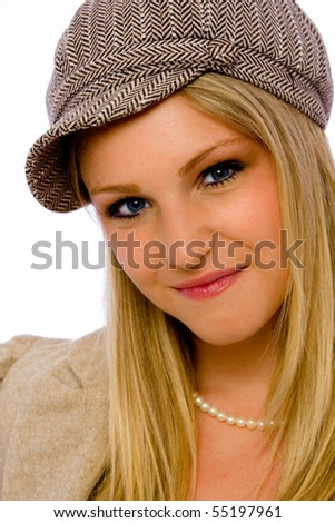 Young blond woman wearing mod cap smiles at camera - stock photo